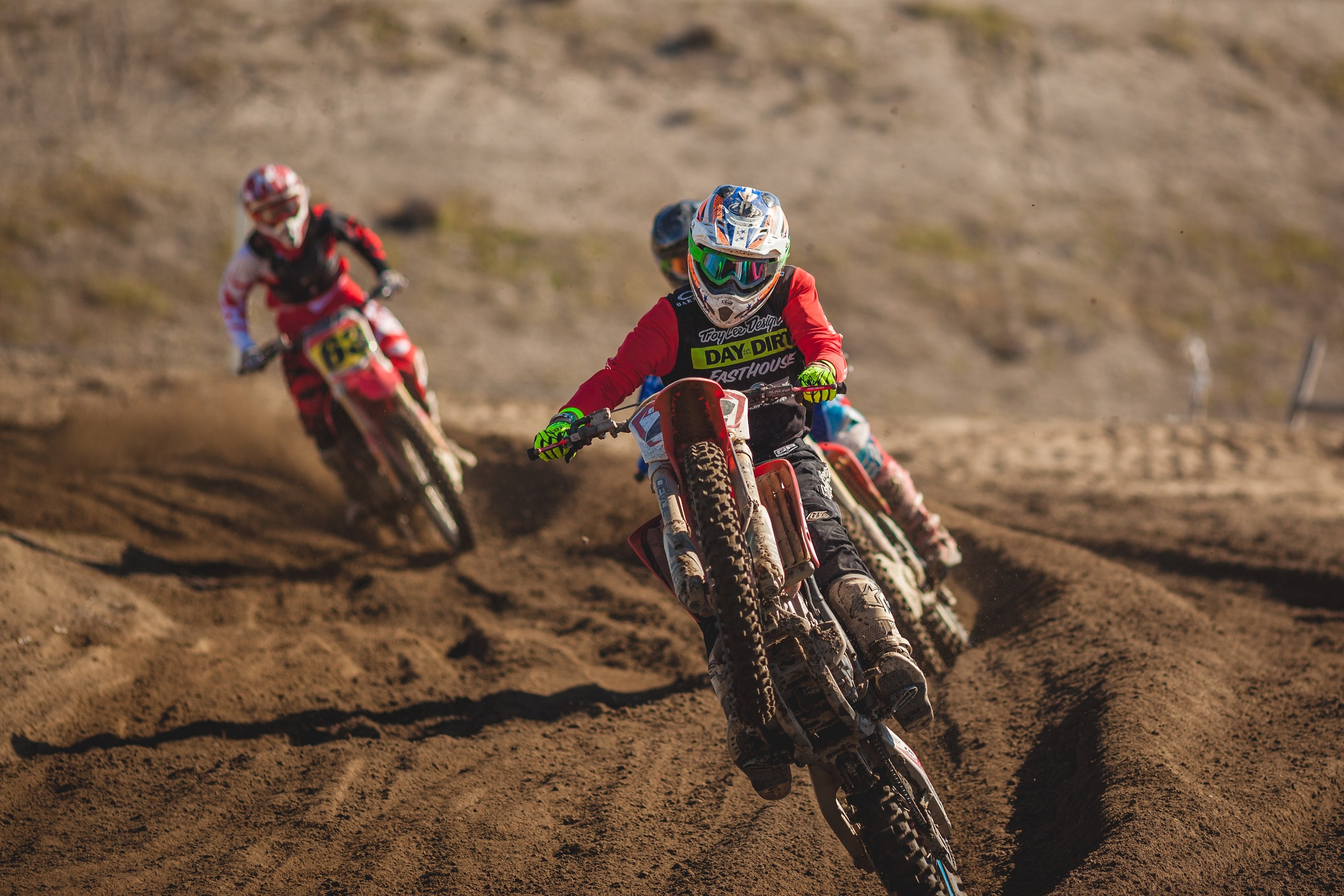 Dirt bike riders racing in fierce competition on a track.
