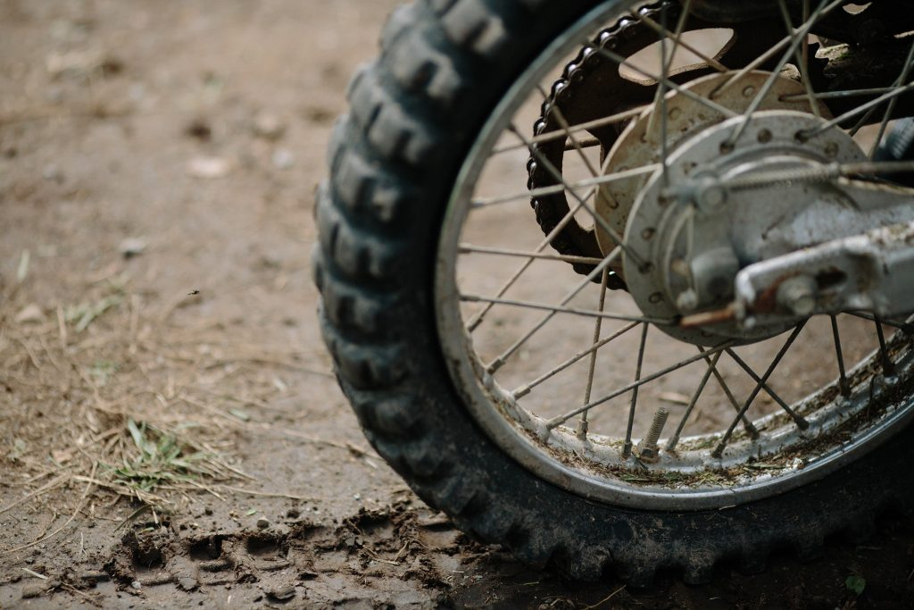 A rear dirt bike tire rests on muddy ground.