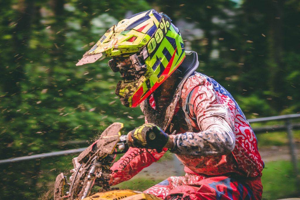 A dirt bike rider's helmet gets splattered with mud as they go around the track.