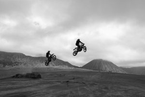 Two dirt bike riders take a jump in an old gravel pit, soaring through the air.