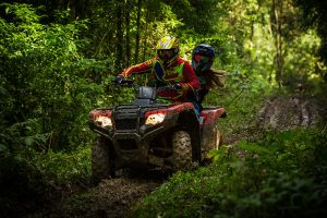 Two people ride on a red ATV in the forest wearing full protective gear.