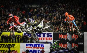 Three dirt bike riders fly through the air as they race around a track with packed stands.