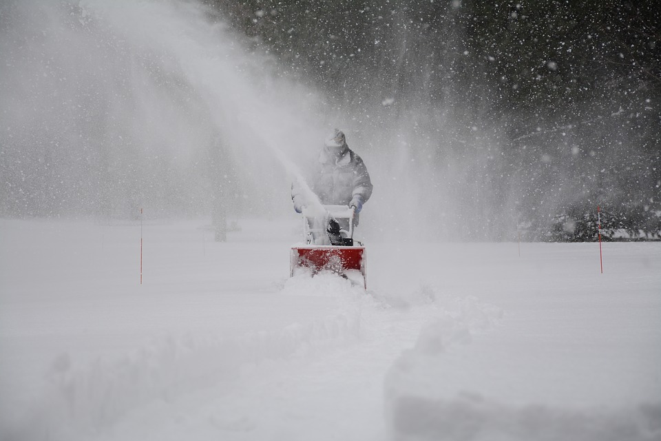 A man clears snow with a Honda snowblower in the dead of winter.
