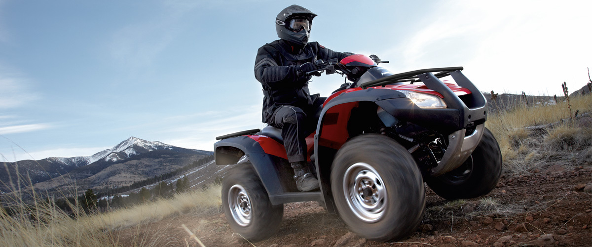 Man riding on a red Honda ATV in the mountains