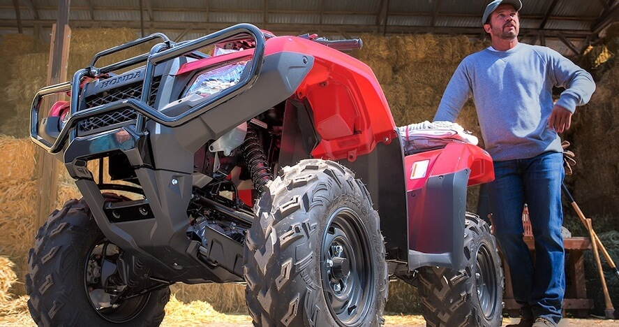 man stands next to his Honda ATV with maintenance tools around him