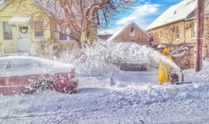 man wearing yellow snow suit clears snow from his driveway with a snowblower