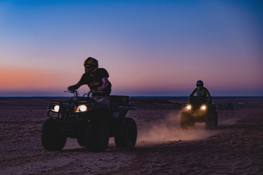 Two atvs riding during sunset