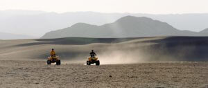Two people riding ATVs through the desert